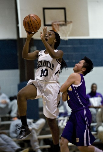 Shenandoah Valley Academy's Salima Omwenga goes up for a layup off a fast break while Massanutten Military Academy's Fan Huang runs into her for a foul during first half girls basketball action Thursday night in New Market.  Rich Cooley/Daily